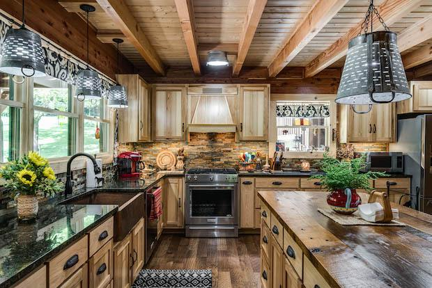 photo of log home master kitchen with exposed beam ceiling, wood flooring and wood cabinets large wood island and farm sink