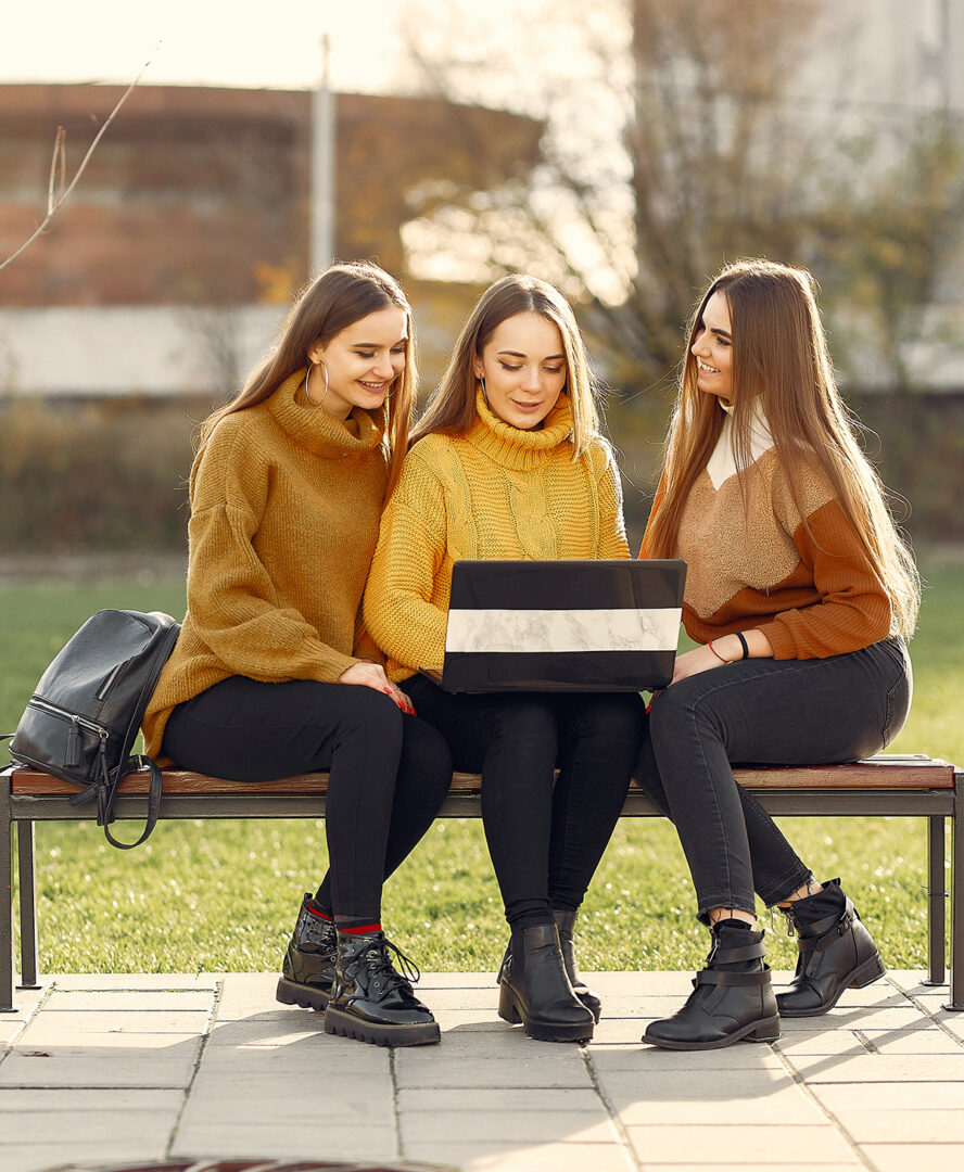 positive-girlfriends-using-laptop-on-bench-4172959