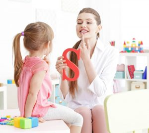 An image of a therapist teaching a child to pronounce the letter S at Learn and Grow Therapy