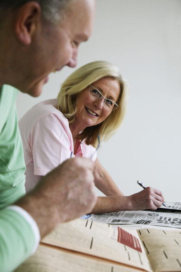 Couple enjoying newspaper crossword together.