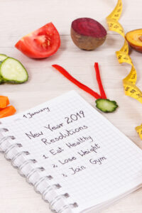 New year resolutions for 2019 and clock made of fresh fruits with vegetables and centimeter