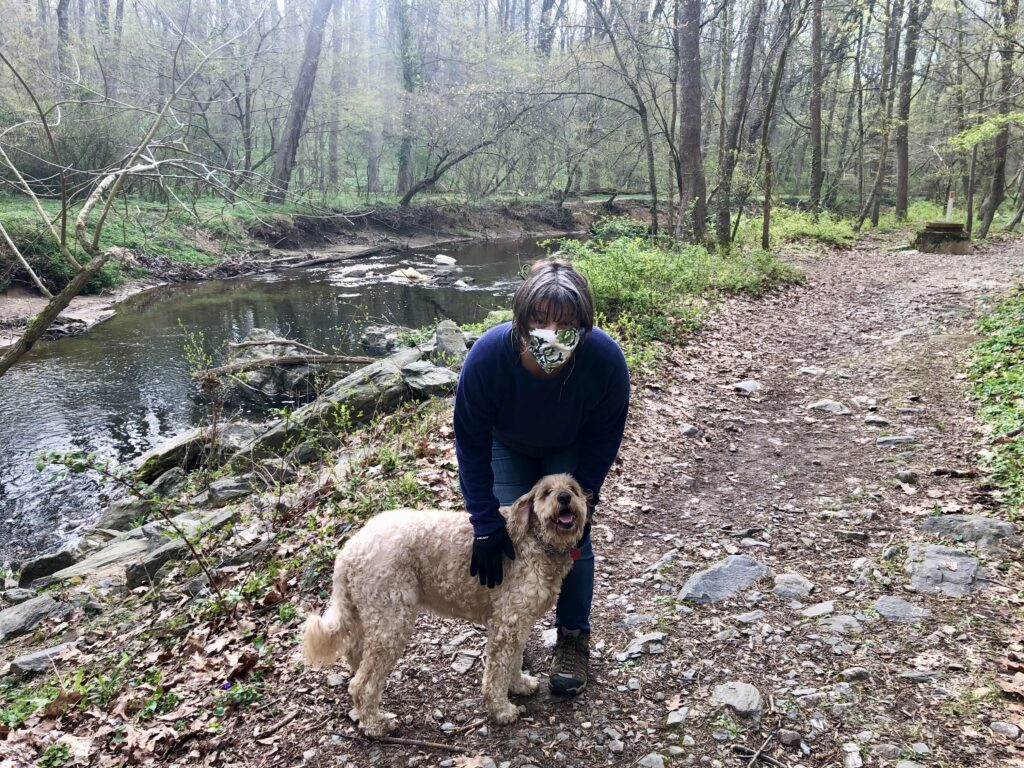 A person and a dog in a forest  Description automatically generated
