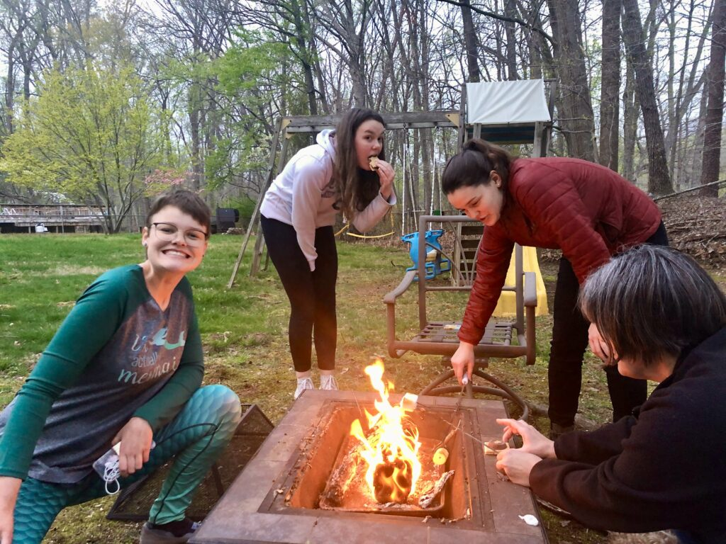 A group of people standing around a fire  Description automatically generated
