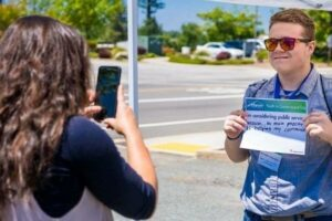 Student demonstrates interest in public service with handwritten sign.
