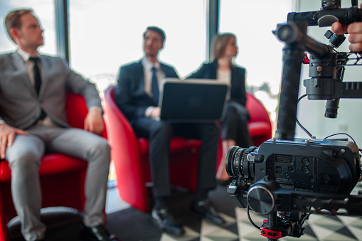 Videographer filming group of people at business meeting