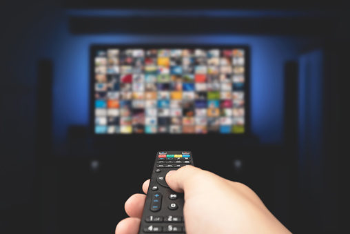 Multimedia video concept on TV set in dark room. Man watching TV with remote control in hand.
