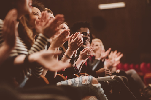 Group of people clapping hands in the theater, close up of hands. Dark tone.