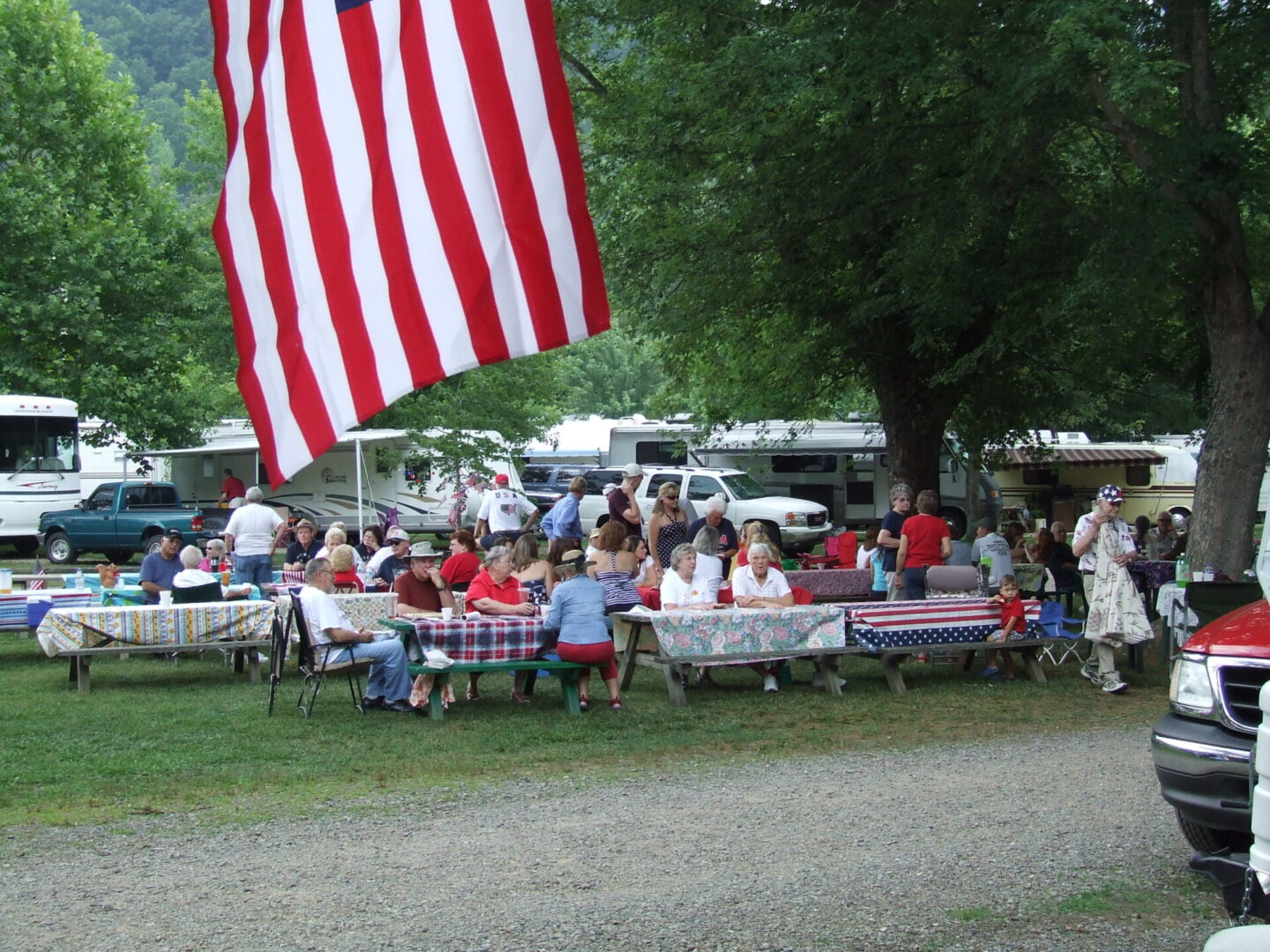 People gathered around on tables in a trailer park