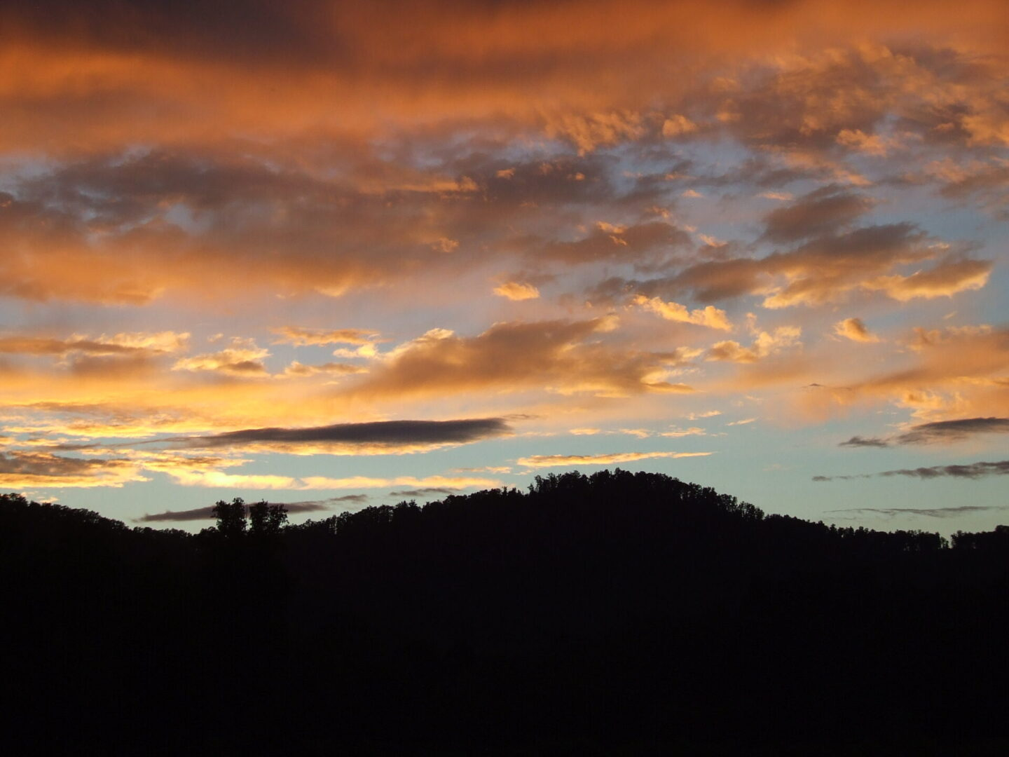 An orange sky with a mountain silhouette