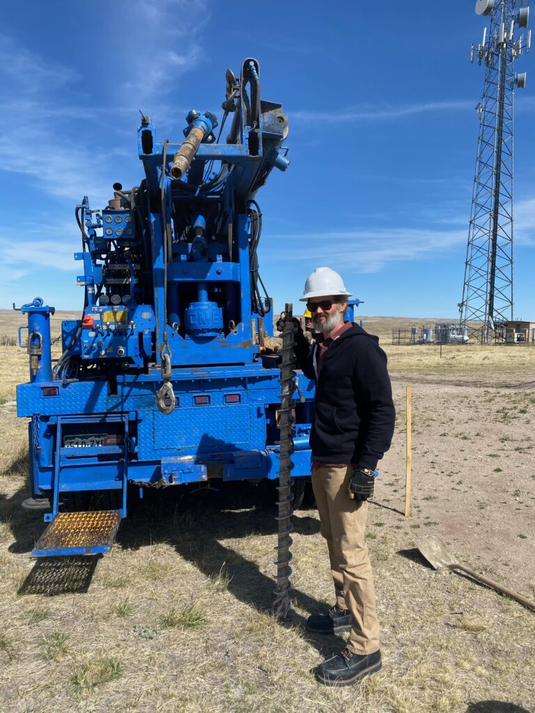 JB Engineers employee standing by some machinery holding a large ground drill bit