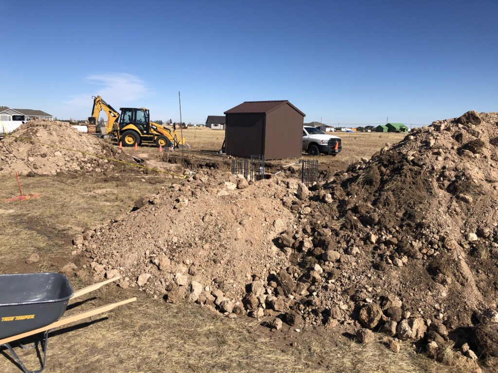 Construction job site with mounds of dirt, wheel barrows, and backhoe loader machinery