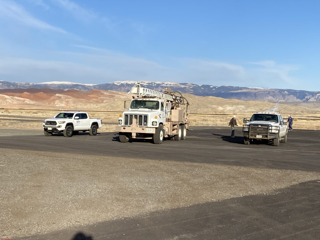 White work trucks on a job site in the Rocky Mountains - JB Engineers