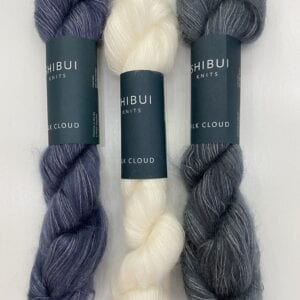A white and two dark colored yarn skeins