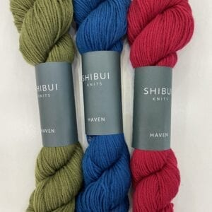 Red, blue, and olive colored yarn skeins