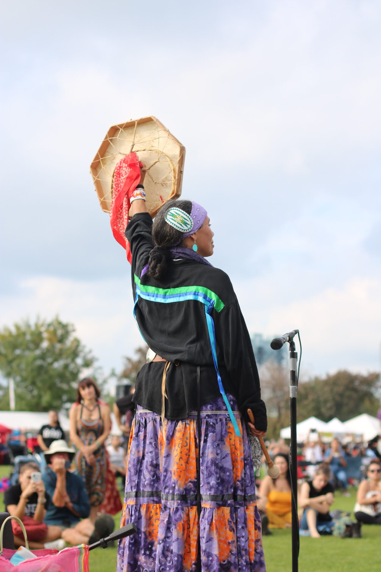 """Indigenous Peoples' Day in New York on Randall's Island is a place for native people to share their chants, songs, and dances, as well as amplify Indigenous stories, movements, and experiences. This event has continued to be held and organized by the Redhawk Native American Arts Council and Cliff Matias since the first event in 2015 when 6000 Indigenous peoples and their supporters gathered on Randall's Island to celebrate the 523 year survival of First Nations cultures and traditions. They created this event to protest """"Columbus Day"""" and show that Indigenous peoples predated Columbus' arrival and that their descendants have not forgotten their origins. For those people who were colonized or subjugated with violence and grief due to the arrival of foreigners, this day evokes the rethinking of Columbus Day by instead focusing on Indigenous peoples and honoring their cultures and traditional practices. So much of history romanticizes western colonization, when it should instead highlight Indigenous stories and how their lives were permanently impacted by the arrival of foreigners. It is important to acknowledge and listen to these stories in order to understand how it is continuing to affect Indigenous people today."""