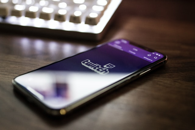 The photo shows a mobile phone with the Twitch logo on it.