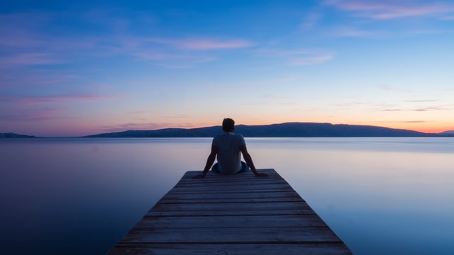 "A photo of a person sitting on a dock, possibly asking themselves the question ""What should I do with my life?"""