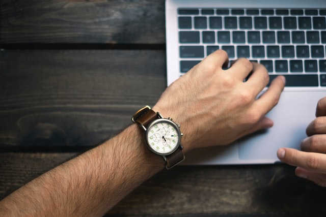 A person checks their watch while working on a computer. This article is about how to be more productive by being aware of time.