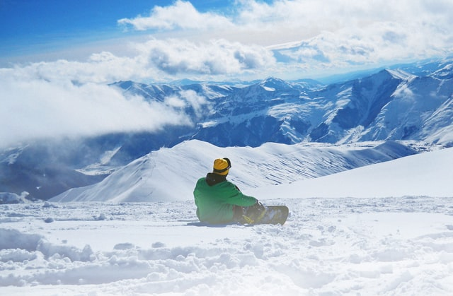 This photo shows a snowboarder sitting on a mountain. Snowboarding is an example of a passion someone could have.