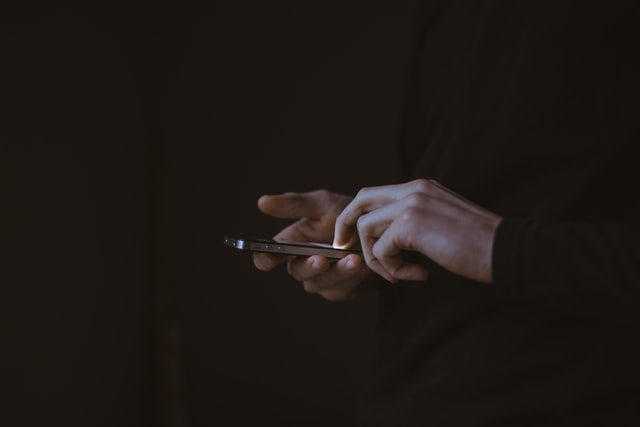 This photo shows the hands of a person using a smartphone. If you are wondering how to stop procrastination then taking a break from social media apps can be a good idea.