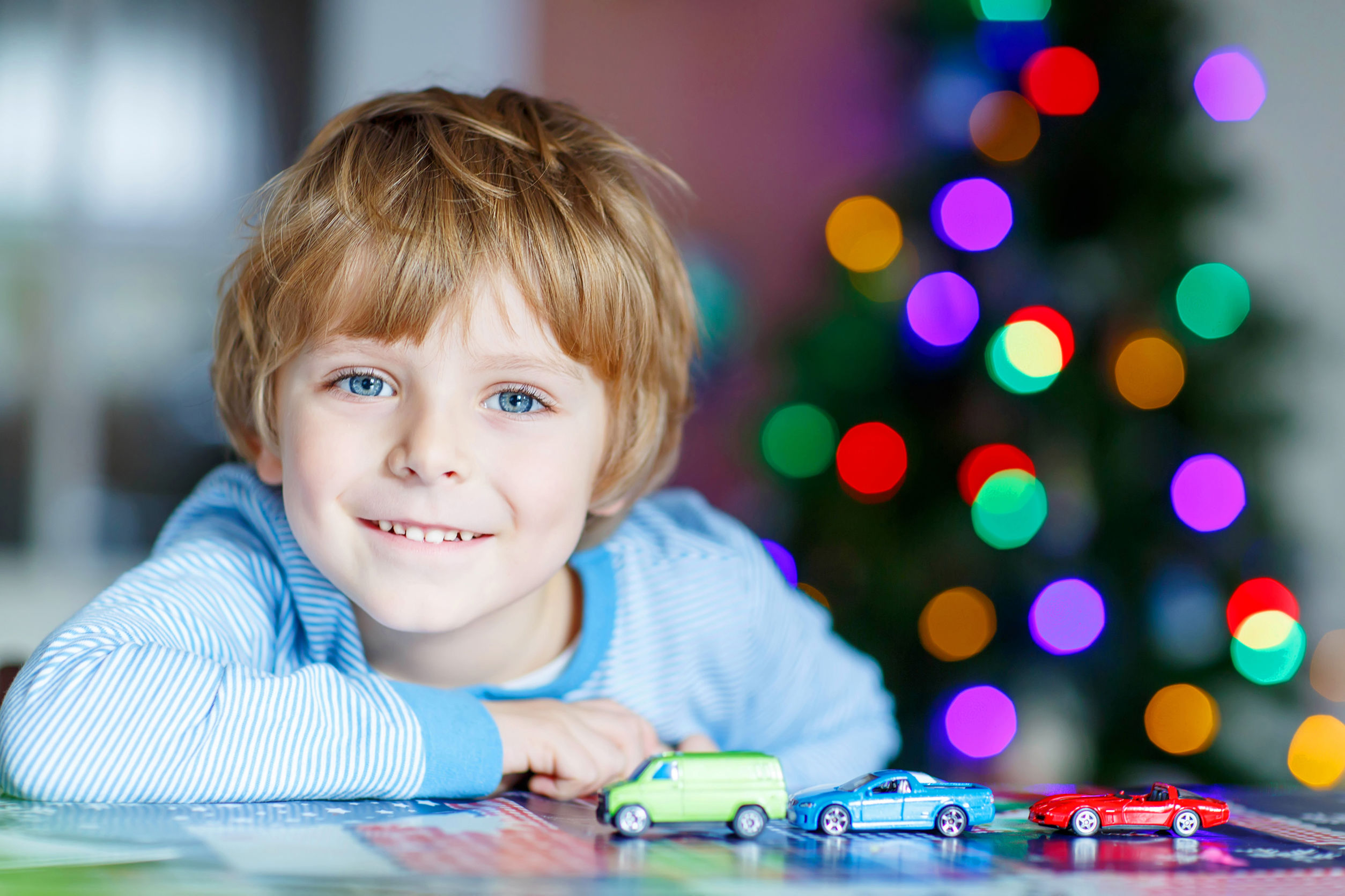 Adorable kid boy playing with cars and toys at home, indoor. funny child having fun with gifts. Colorful christmas lights on background. Family, holiday, kids lifestyle conceplt.
