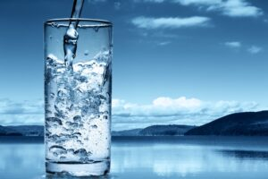 Glass of water being filled mountains and sky in background