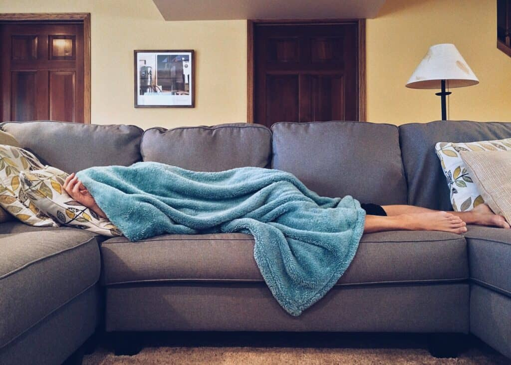 man covering himself with blue weighted blanket