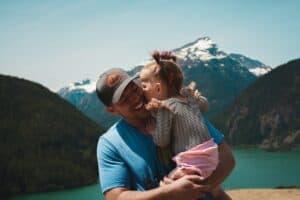 man carrying little girl