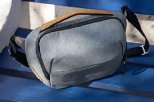 blue floor holding grey sling bag