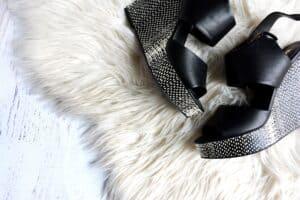 black wedge sandals on white carpet