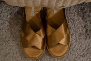 golden sandals on grey carpet