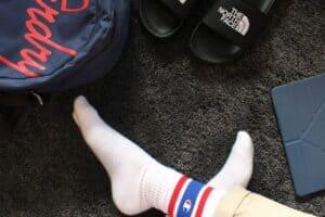 black slides beside person wearing white champion socks
