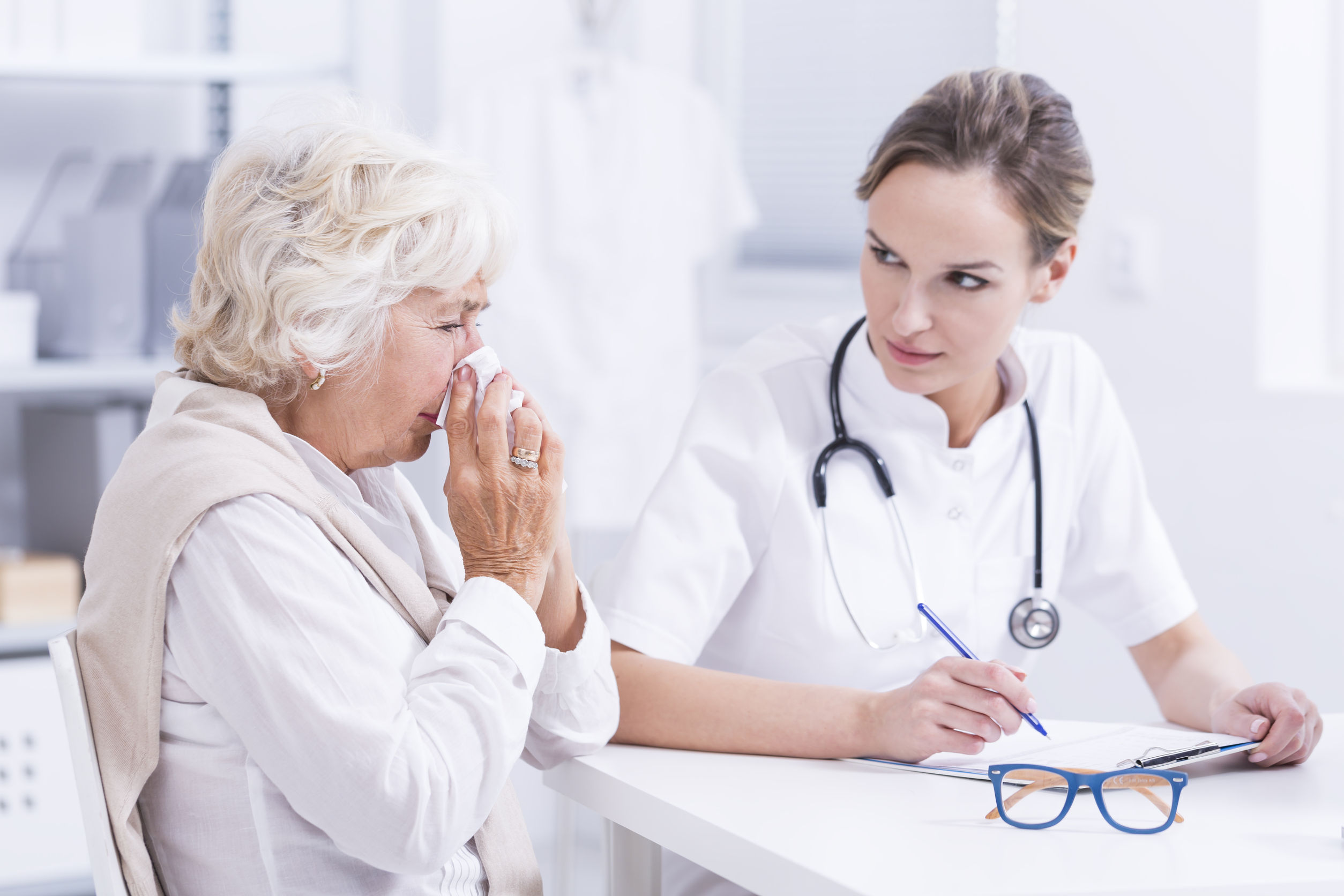 Senior Woman During Visit At Allergist, Doctor Doing Notes