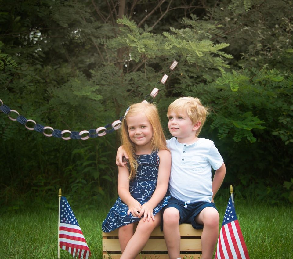 Picture of two siblings sitting next to flags on 4th of July
