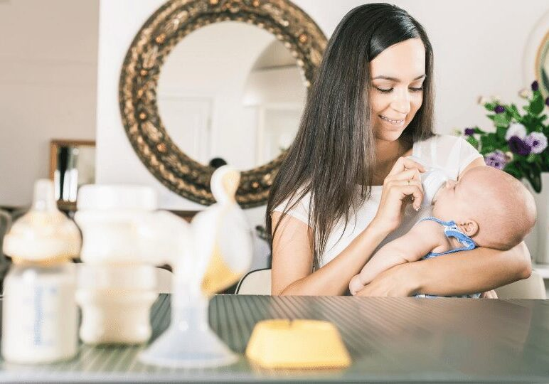Mother bottle feeding her infant with breast pump parts shown