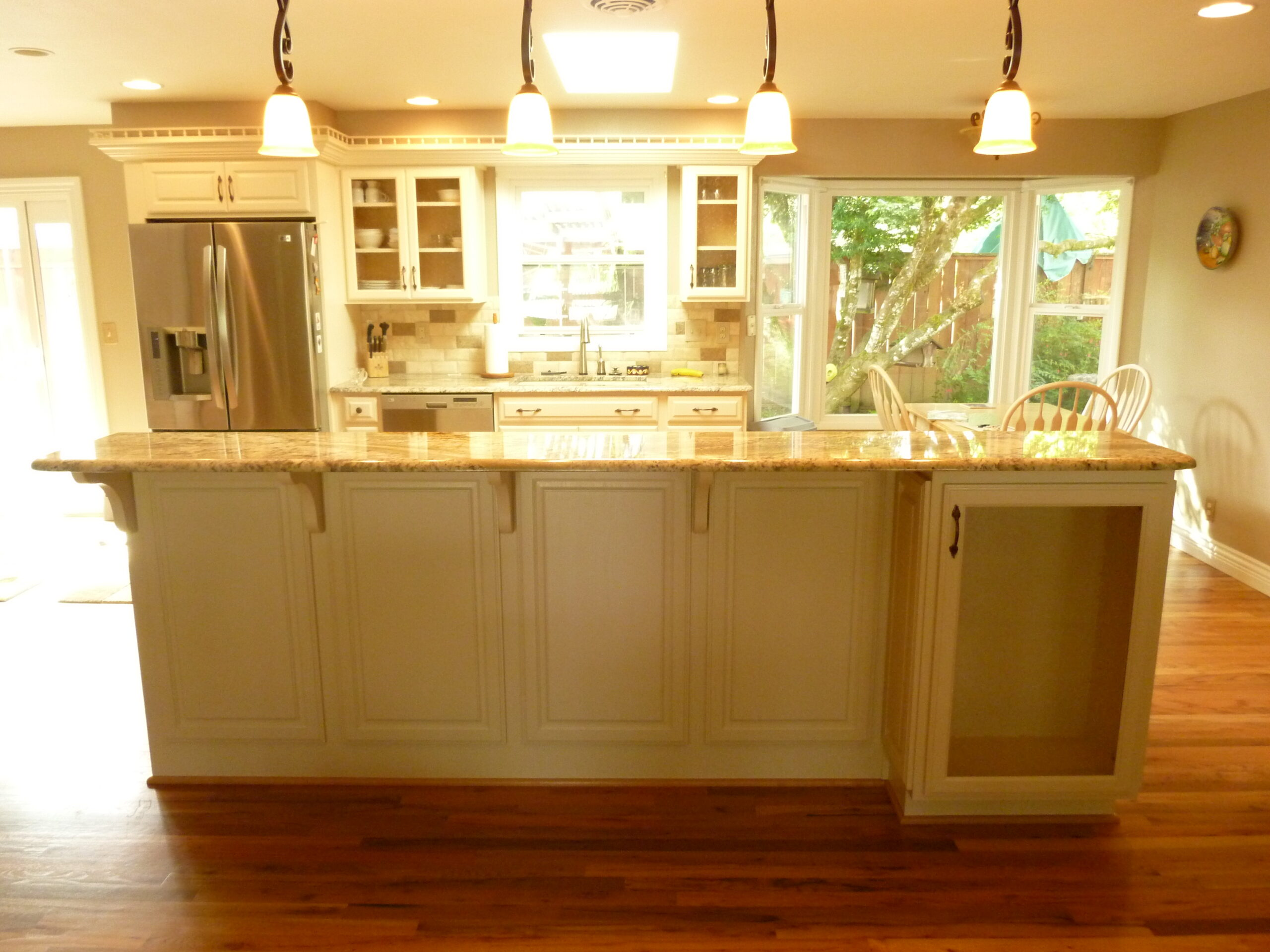 View from behind kitchen island facing sink and refrigerator