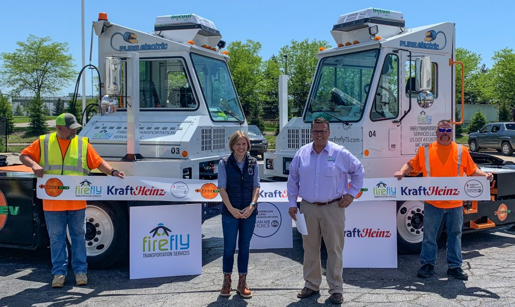 Ribbon-cutting ceremony for Kraft Heinz deployment of Orange EV pure electric terminal trucks via Firefly Transportation Services. Pictured at center: Erin Mitchell, Head of Warehousing for The Kraft Heinz Company, and Mike Bohnstengel, Principal Partner at Firefly Transportation Services.