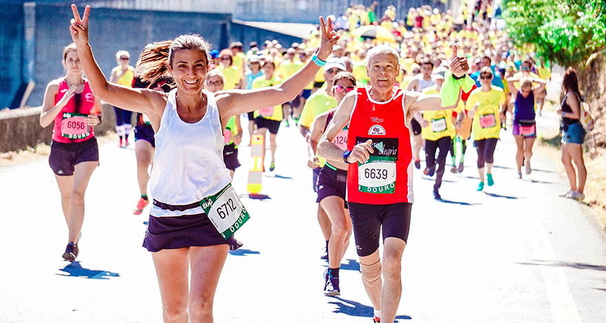 woman finishing a race with a crowd behind her