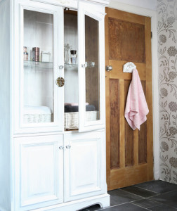 White bathroom, large white display cabinet, varnished wood door, pink towel, grey floor tiles. Pub orig IH 02/2009 Real home