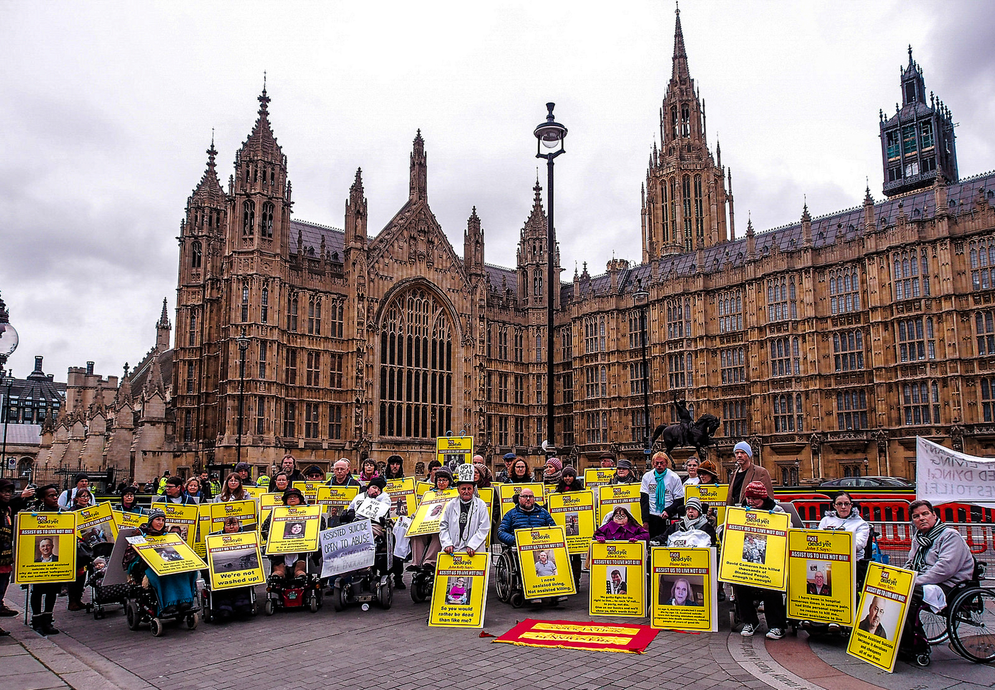 Picture of disabled people and supporters demonstrating outside parliament.