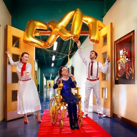 Liz Carr sitting in a gold wheelchair underneath the word Exit formed by golden balloons