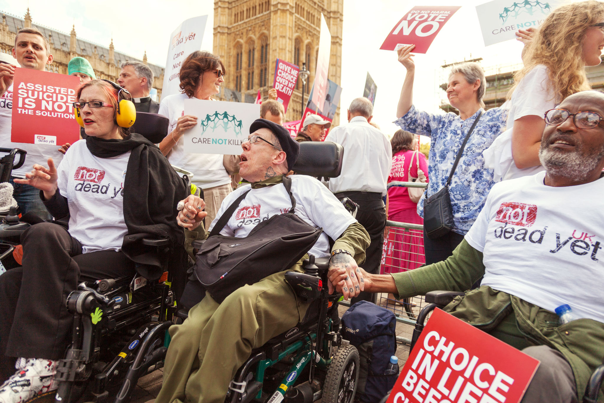 Activists for Not Dead Yet UK cheer during a rally of support for disability rights.