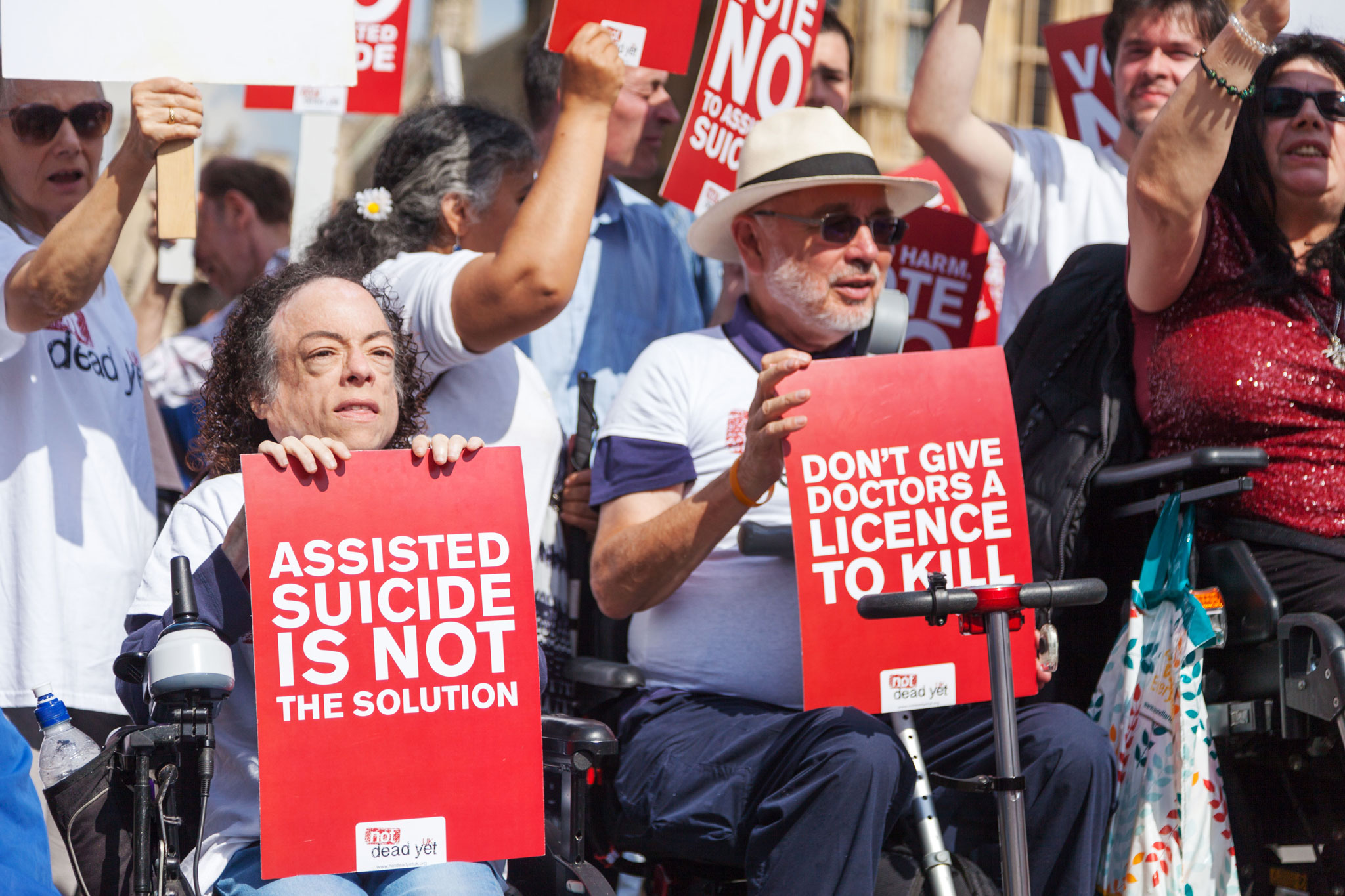 "Activists from Not Dead Yet UK are gathered with signs reading ""Assisted Suicide is Not the Solution"" and ""Don't Give Doctors a Licence to Kill."""