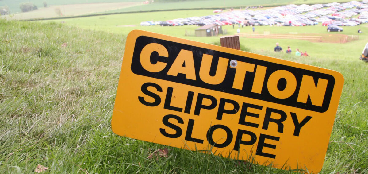 A sign post in a sloping field which says Caution Slippery Slope