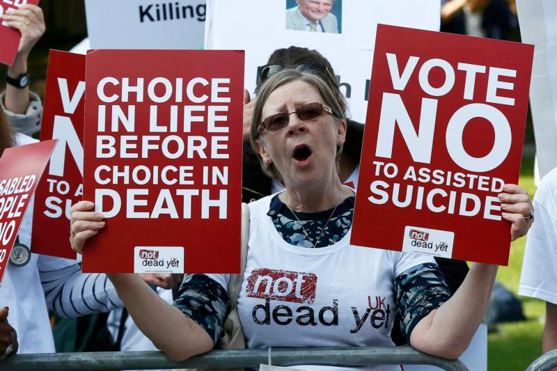 Protester holding placards saying Vote No to Assisted Suicide
