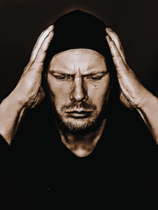 Distraught man with hood on and facial hair gripping his head with his hands