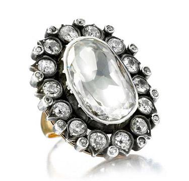 A Diamond Ring set with a central flat old mine-cut cushion-cut diamond