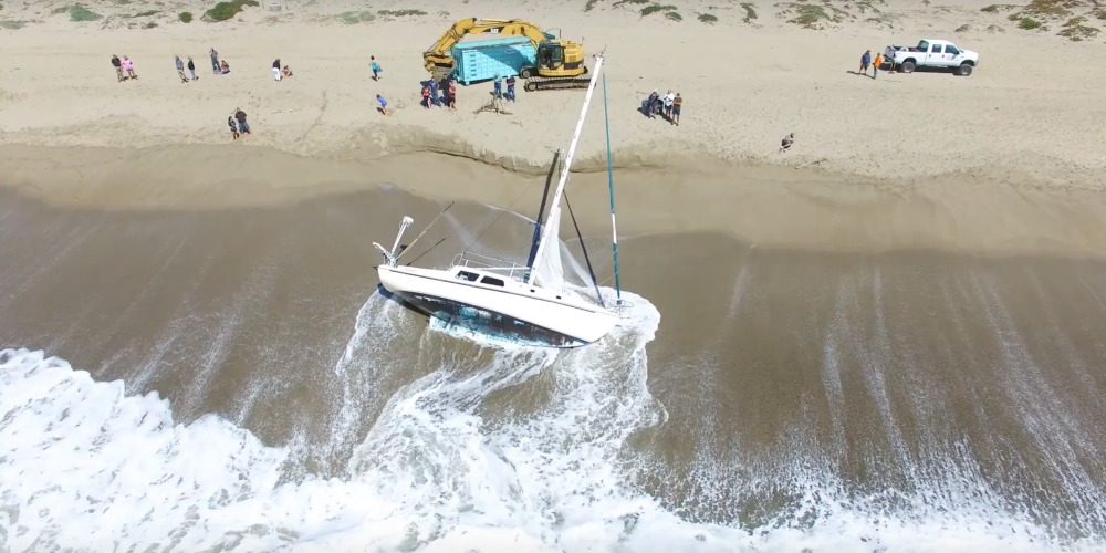"""Photo of A Man Will Always Love His Boat: the Aerial """"FUNERAL"""" For A Beached Sailboat"""