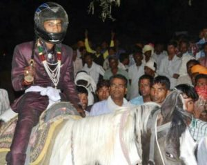 The bridegroom in a helmet on a horse