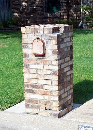 Image of Damaged Brick Mailbox shifted on its foundation from being hit and damaged.